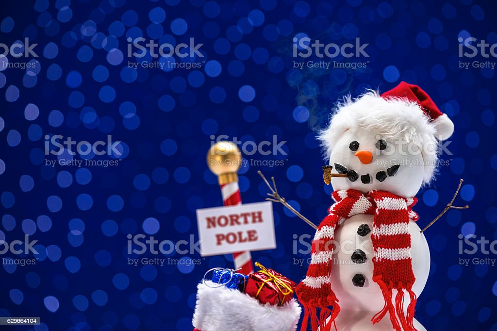 Snowman wearing Santa Hat with a bag of presents stock photo
