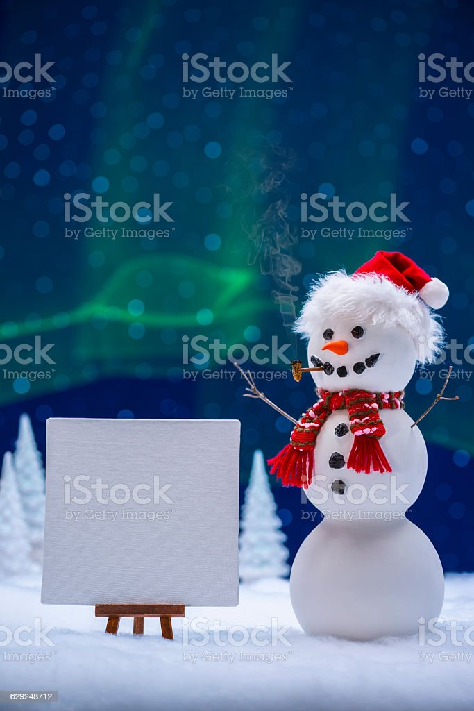 Snowman wearing Santa Hat with blank sign and Aurora Borealis stock photo