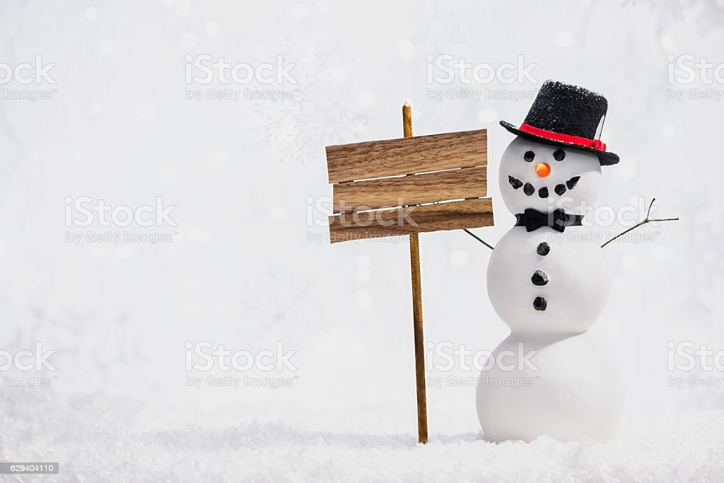 Snowman wearing Top Hat with blank sign in snowy scene stock photo