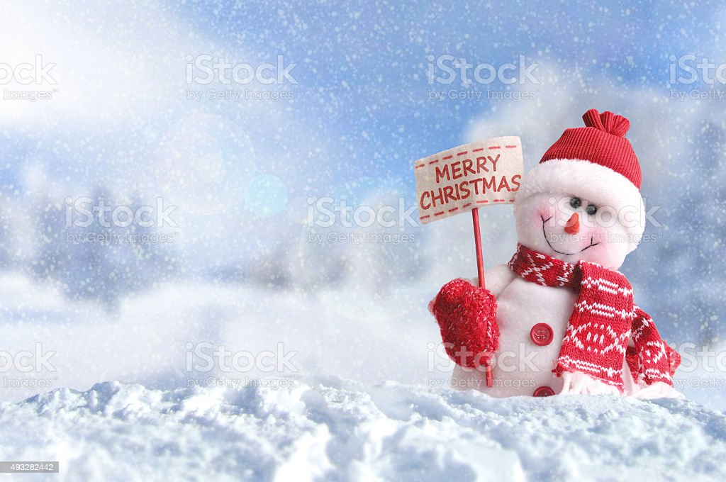 Snowman with a placard Merry Christmas on the snow stock photo