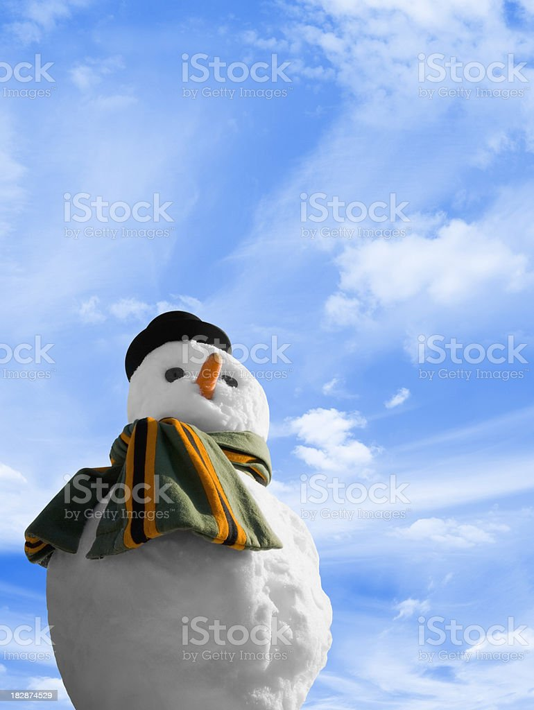 Snowman with green and orange scarf against blue sky royalty-free stock photo