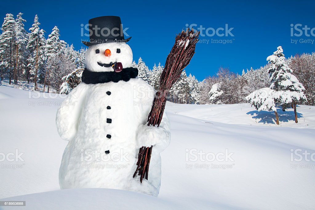 Snowman with stovepipe hat, pipe and broom in the forest stock photo