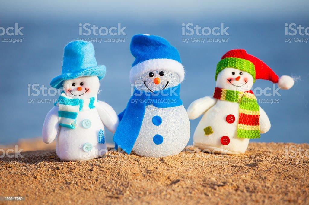 Snowmans on sand stock photo