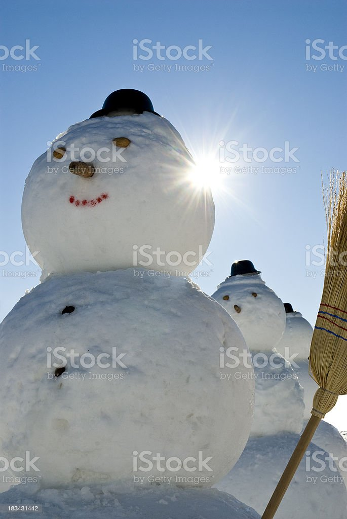 Snowmen Army - Snowman with hat and broom in sun royalty-free stock photo