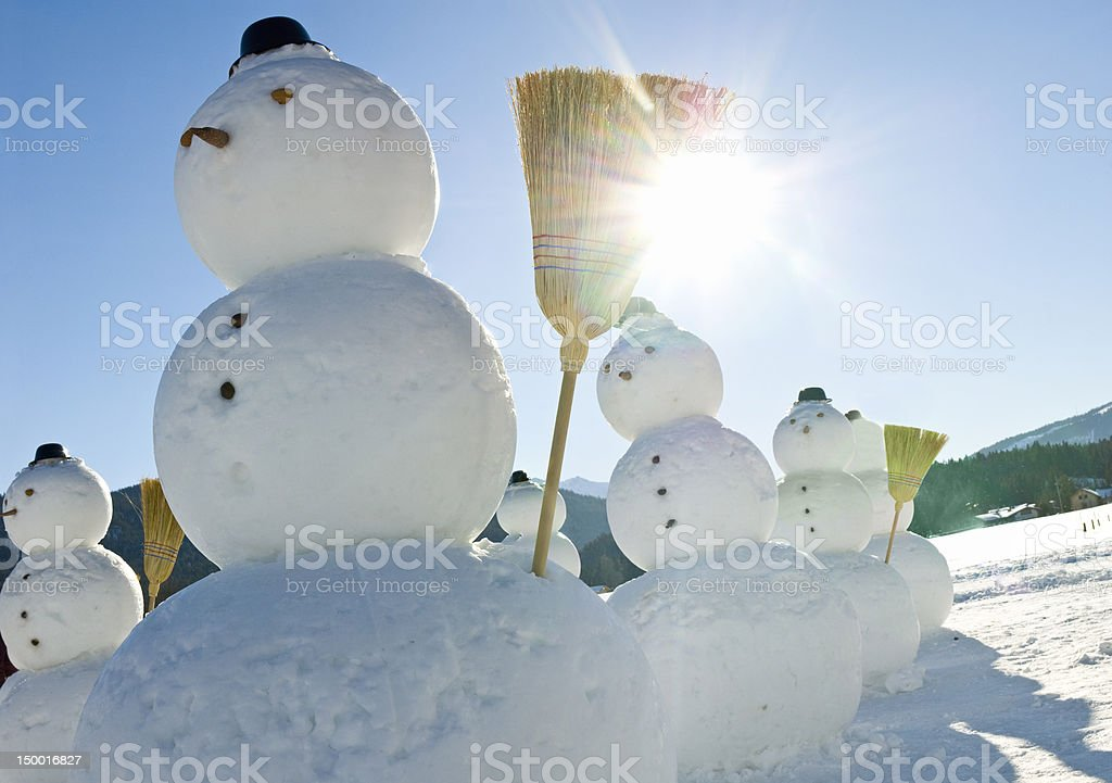 Snowmen Company - Snowman with hat and broom in sun royalty-free stock photo
