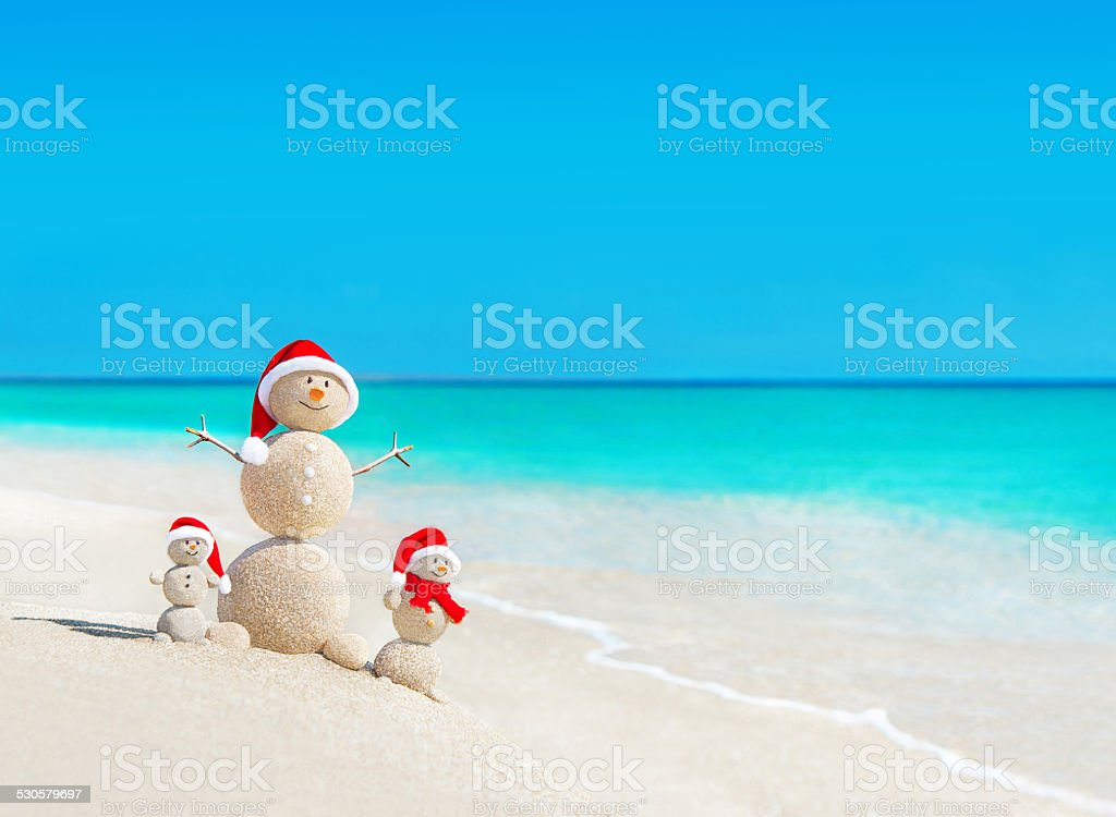 Snowmen family at beach in santa hats.Christmas concept stock photo