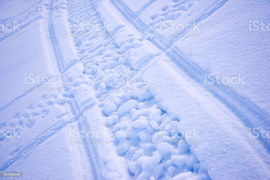 Snowmobile cross tracks in snow pass mountains as background. Winter season. stock photo