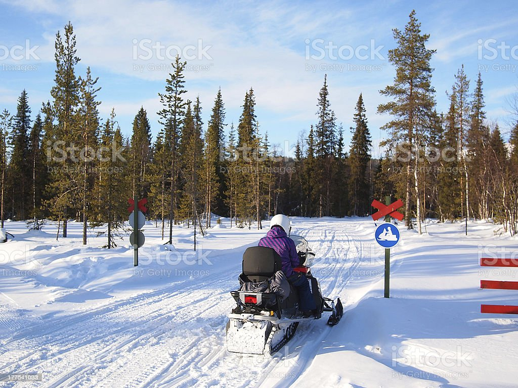 Snowmobile driver stopped on a snowy road in the woods stock photo