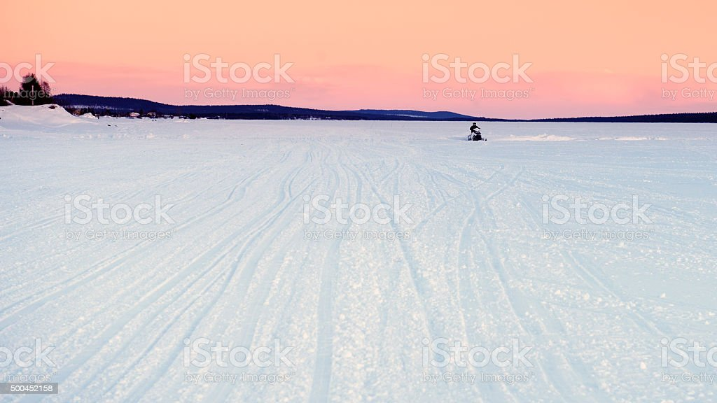 Snowmobile driving on the ice at sunset stock photo