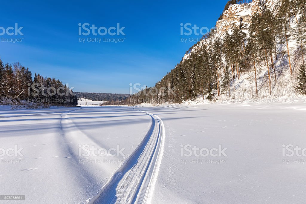 Snowmobile track on frozen mountain river stock photo