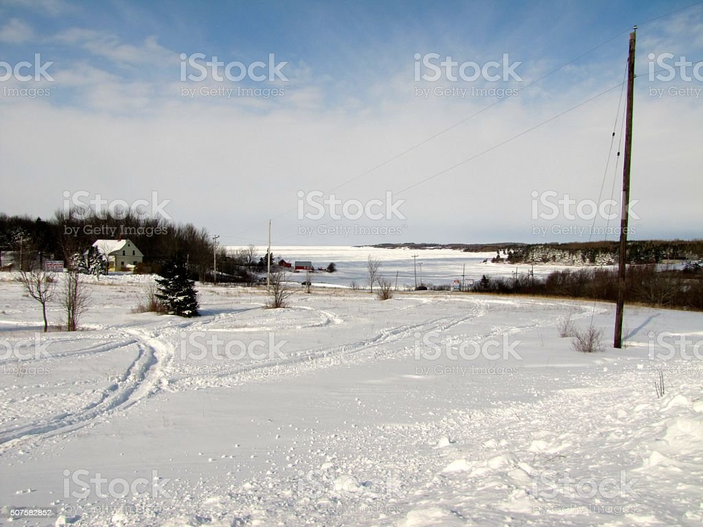 Snowmobile Tracks in Field by Ice Filled Ocean Bay stock photo