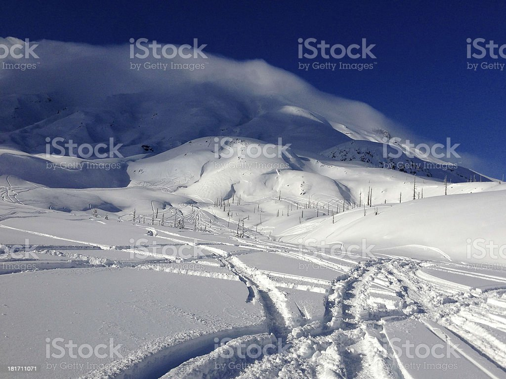 Snowmobile tracks with clouds stock photo