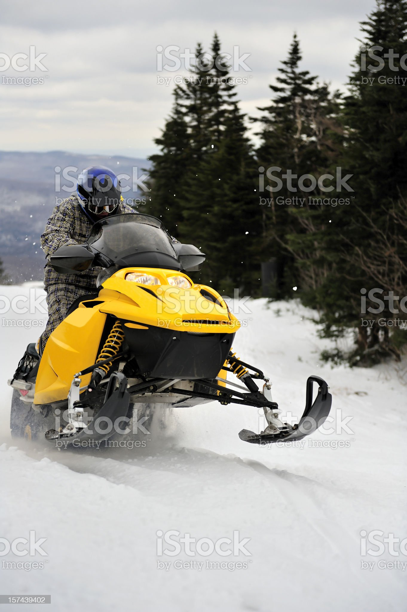 Snowmobiler getting air while riding through a mountain pass royalty-free stock photo