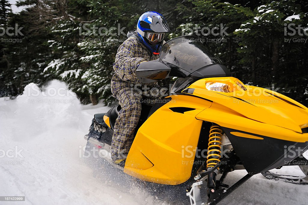 Snowmobiler rides fast through woods leaving trail of snow royalty-free stock photo