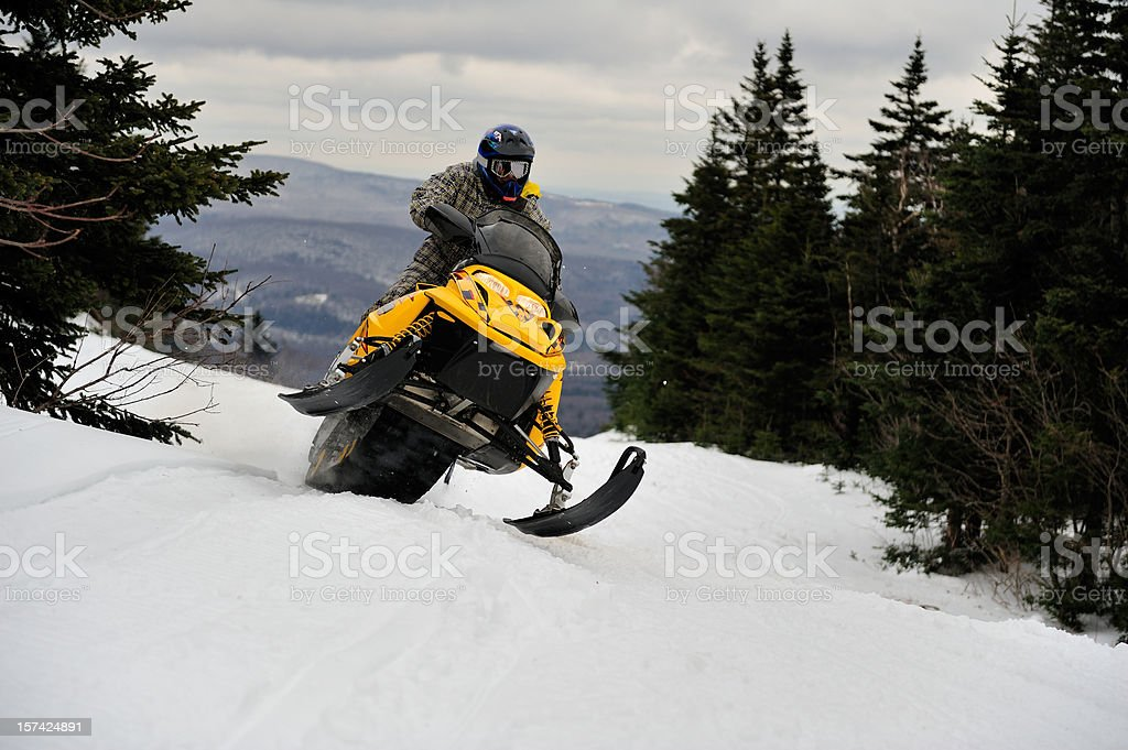 Snowmobiler rides hard and fast through the mountain pass stock photo