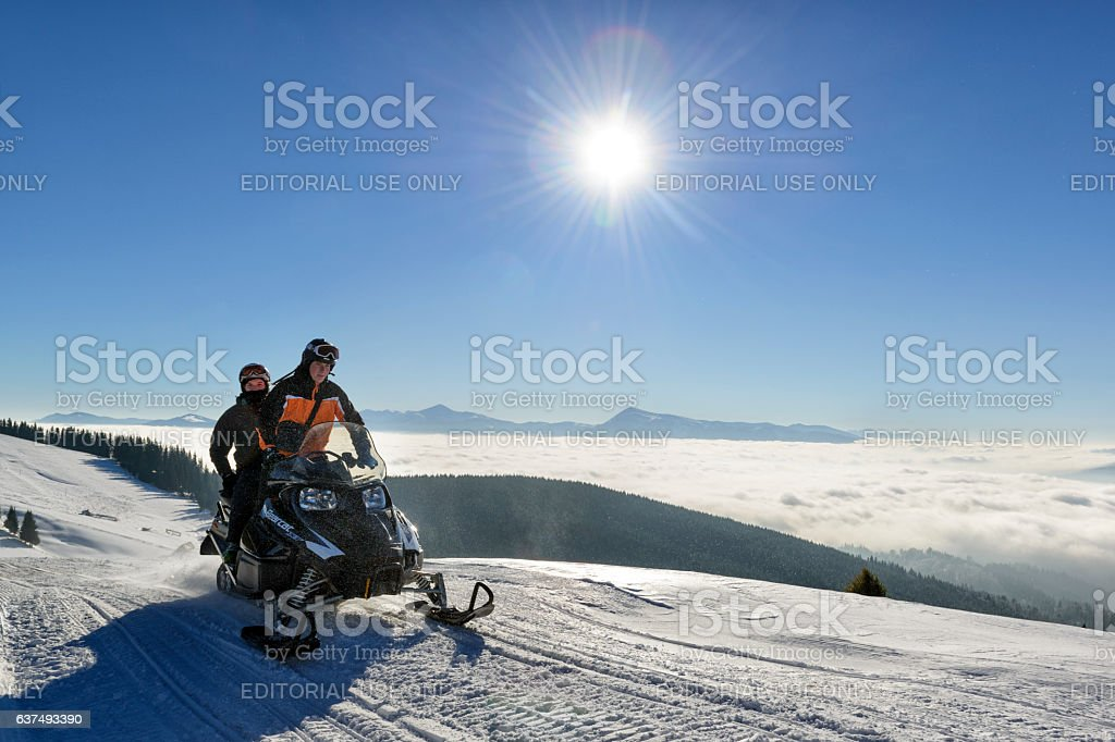 Snowmobiling in mountains stock photo