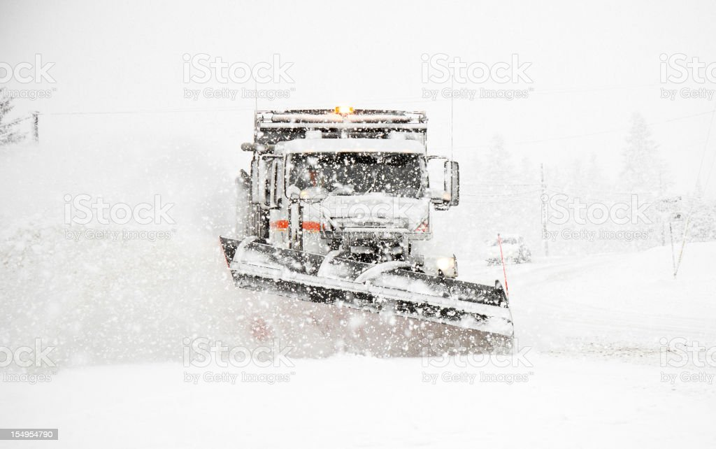 Snowplow Plowing Highway During Large Winter Storm stock photo
