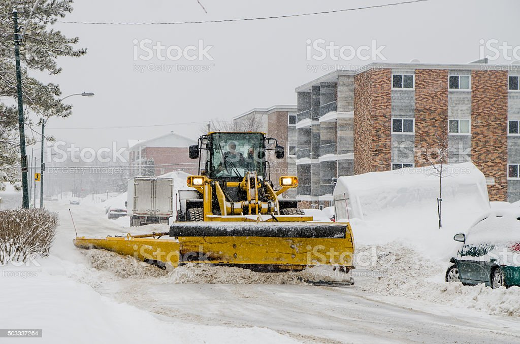 Snowplow pushing snow out of street stock photo