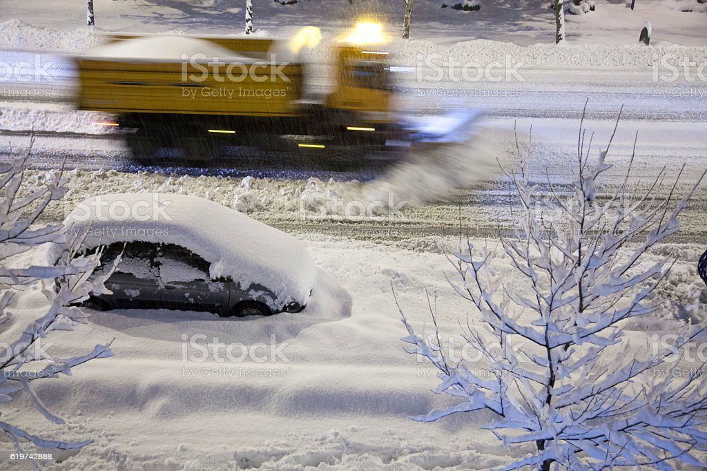 Snowplow removing new snow at night stock photo
