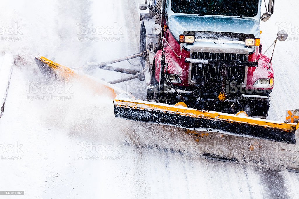 Snowplow removing the Snow from Highway during a Snowstorm stock photo