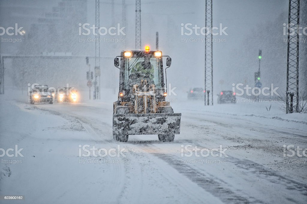 Snowplow tractor on snowstorm road stock photo
