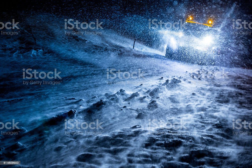 Snowplow Truck Cleaning the Icy Road by Night stock photo