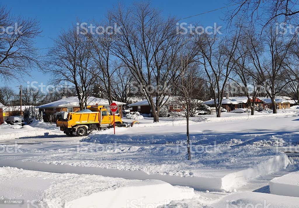 Snowplowing truck on a suburban street. stock photo