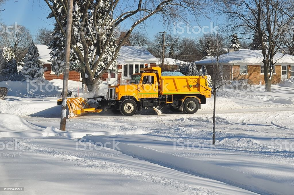 Snowplowing yellow truck on a suburban street. stock photo