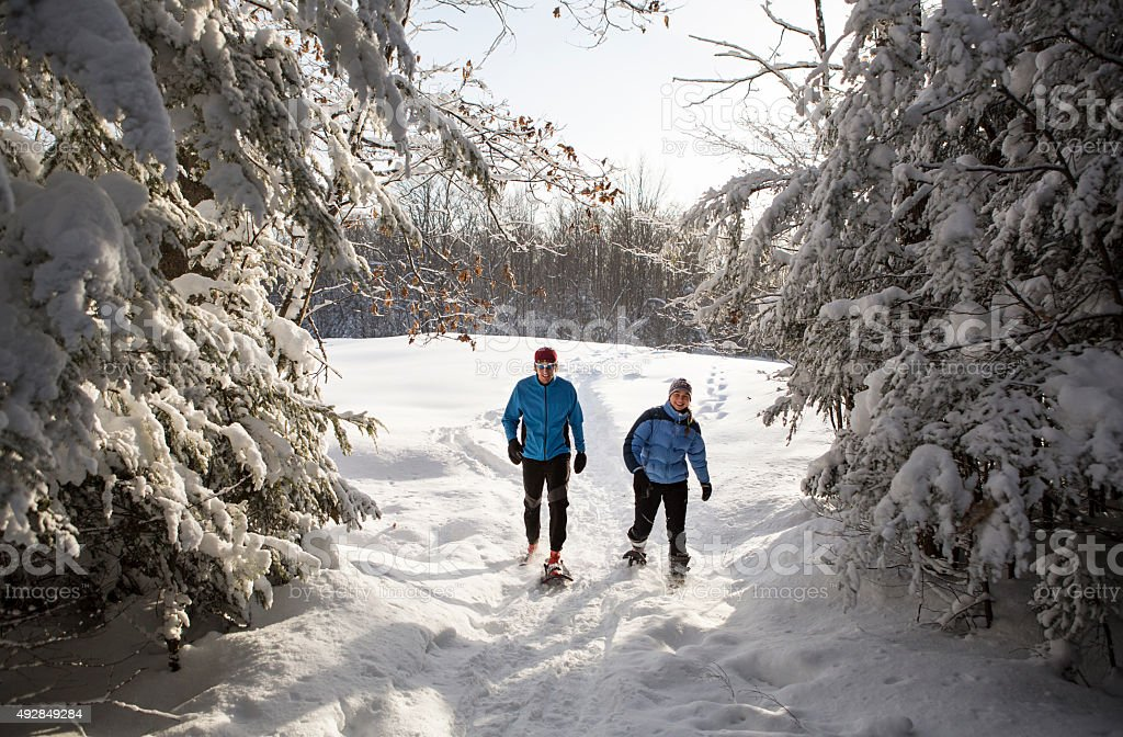 Snowshoeing Couple in The Midwest on a Sunny Winter Day. stock photo