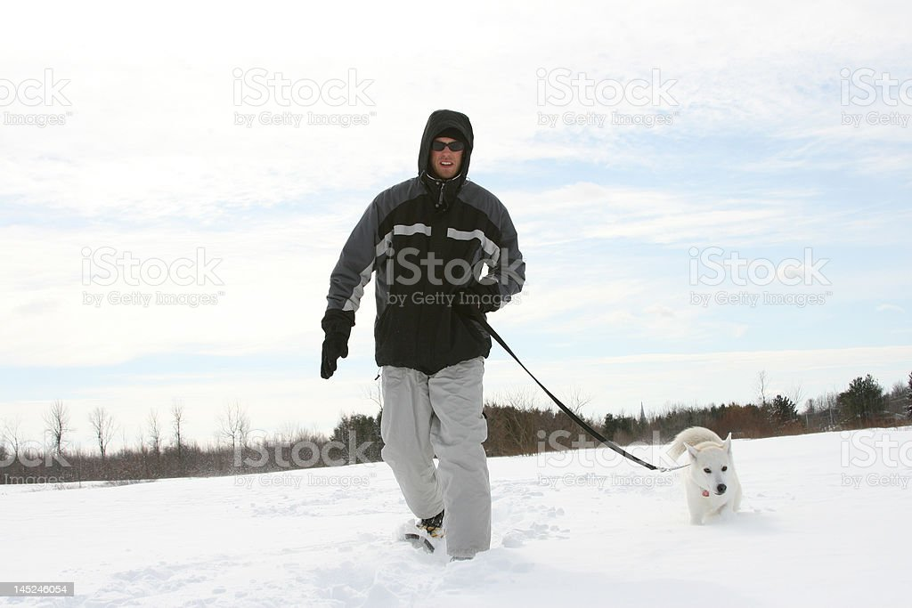 Snowshoeing with his dog royalty-free stock photo