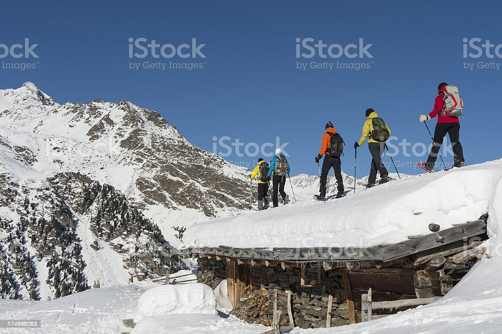 Snowshoers on a roof of hut royalty-free stock photo
