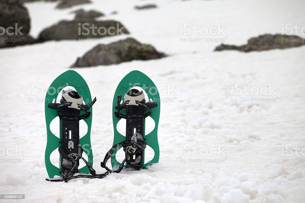 Snowshoes in snowy mountains stock photo