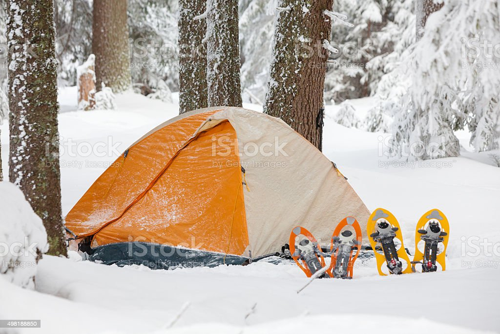 Snowshoes left in front of orange tent in winter forest stock photo