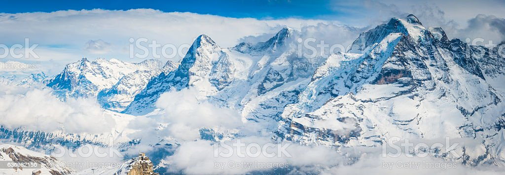 Snowy Alpine peaks Eiger overlooking cable car station Alps Switzerland stock photo