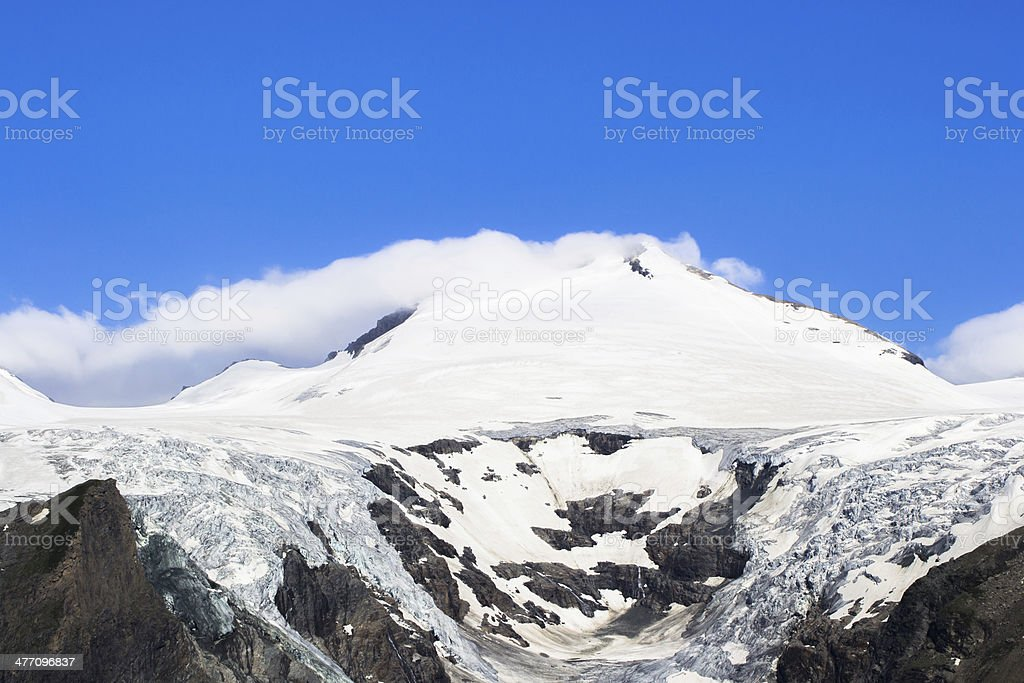 Snowy and cloudy mountain peak with bright blue sky above royalty-free stock photo