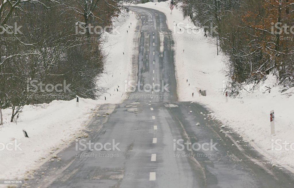 Snowy asphalt road over hills stock photo