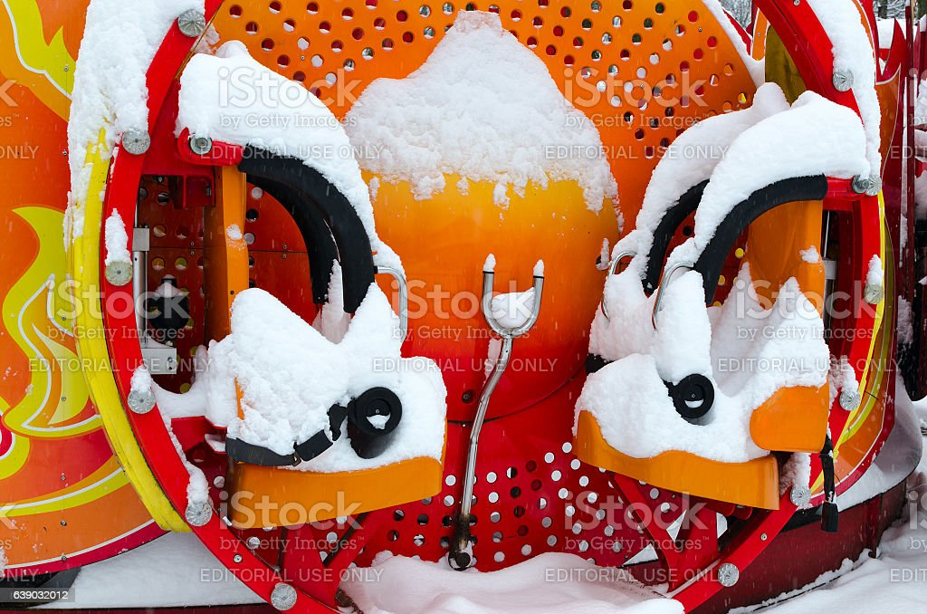 Snowy bright multicolored attraction in winter park during snowfall stock photo