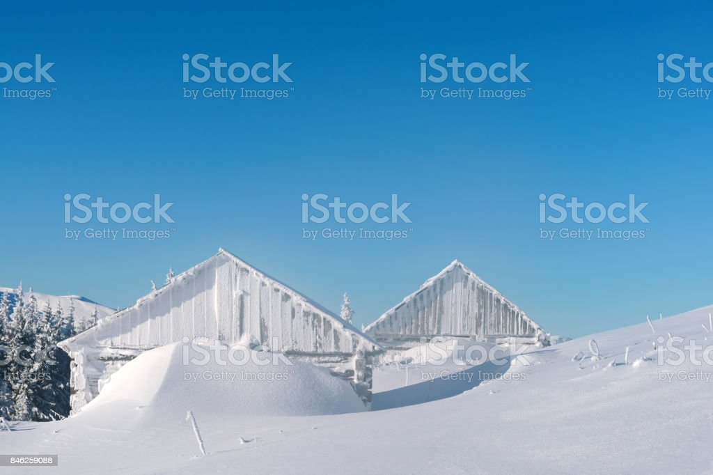 Snowy cabin in the winter mountains stock photo