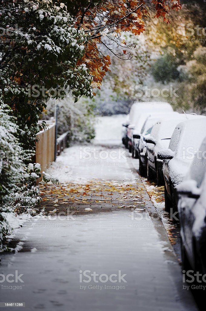 Snowy cars parked in autumn city royalty-free stock photo