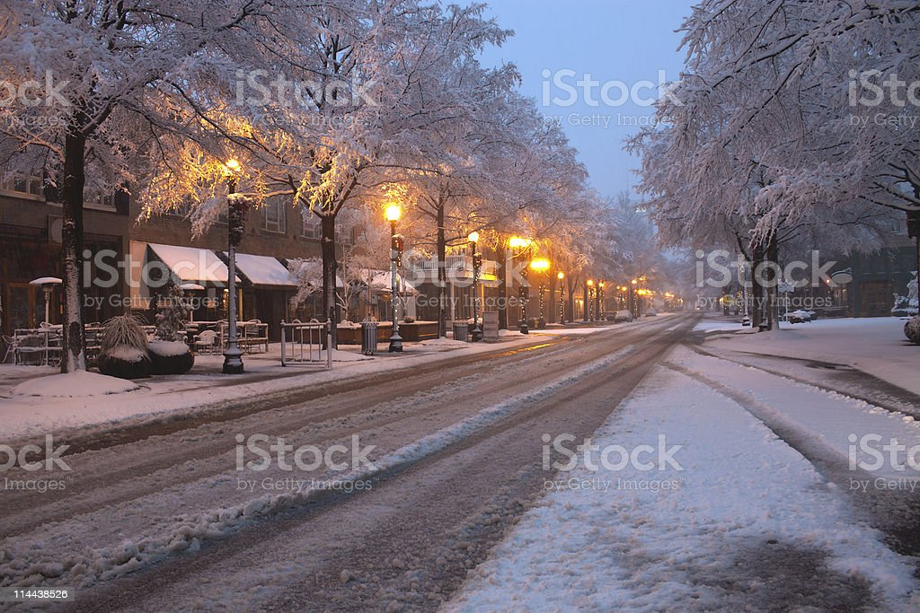 Snowy Downtown Street at Dusk Lit By Street Lights stock photo