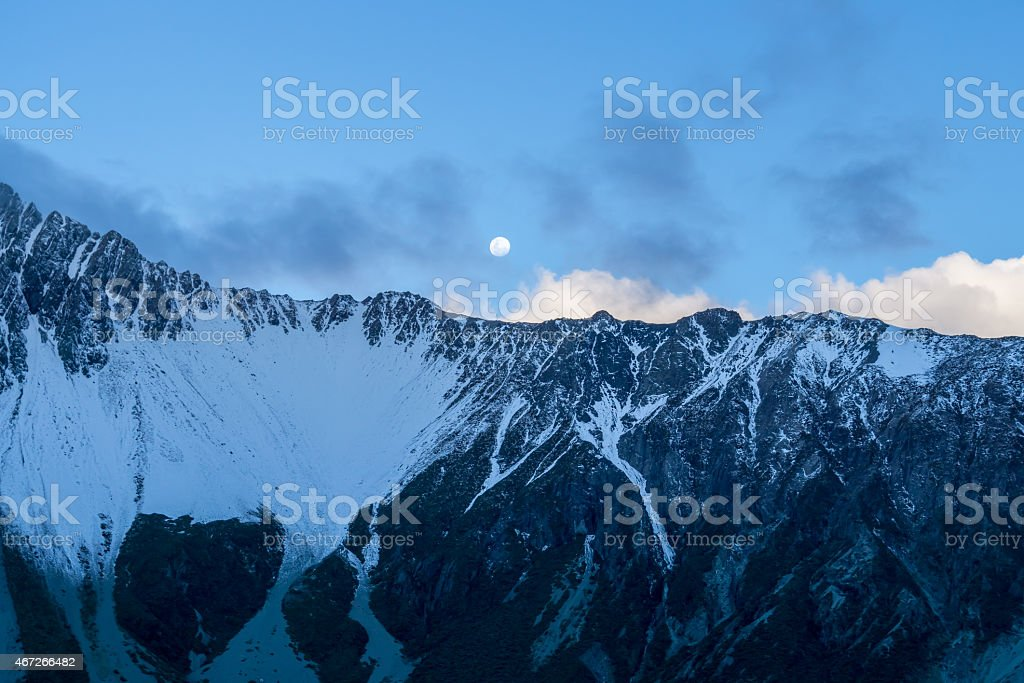 snowy mountain near Mount Cook at dusk with moon rising stock photo