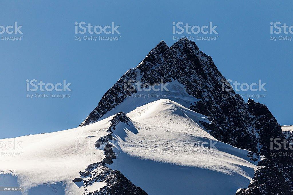 Snowy mountain peak. Mountaineering stock photo