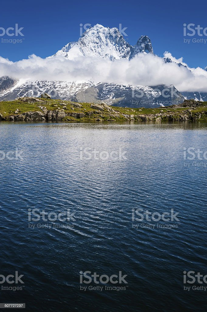 Snowy mountain peak reflecting in tranquil blue lake Alps royalty-free stock photo