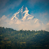 Snowy mountain peak soaring over villages Machapuchare Annapurna Himalaya Nepal
