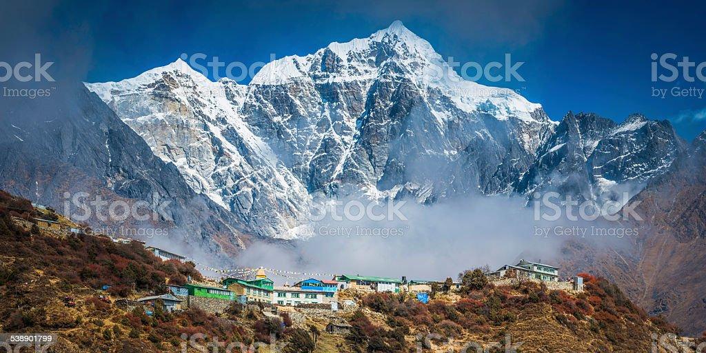 Snowy mountain peak towering over Sherpa teahouses Khumbu Himalayas Nepal stock photo