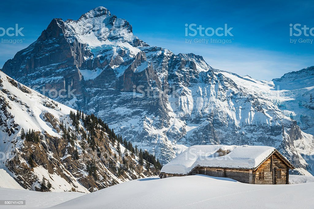 Snowy mountain peaks above traditional wooden chalet Alps Switzerland stock photo