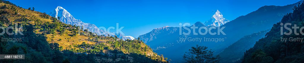 Snowy mountain peaks overlooking vibrant green terraces farms villages Himalayas stock photo