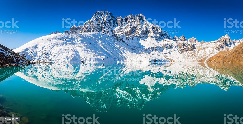 Snowy mountain peaks Phari Lapcha reflecting Gokyo Lake Himalayas Nepal stock photo