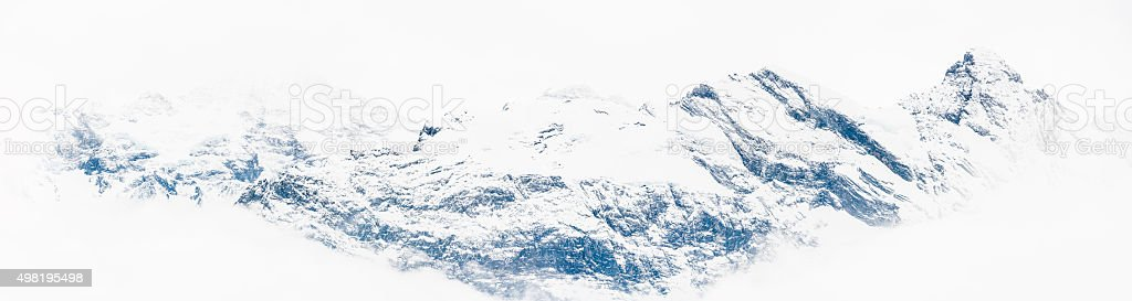 Snowy mountain peaks wild Alpine summits appearing through white mist stock photo