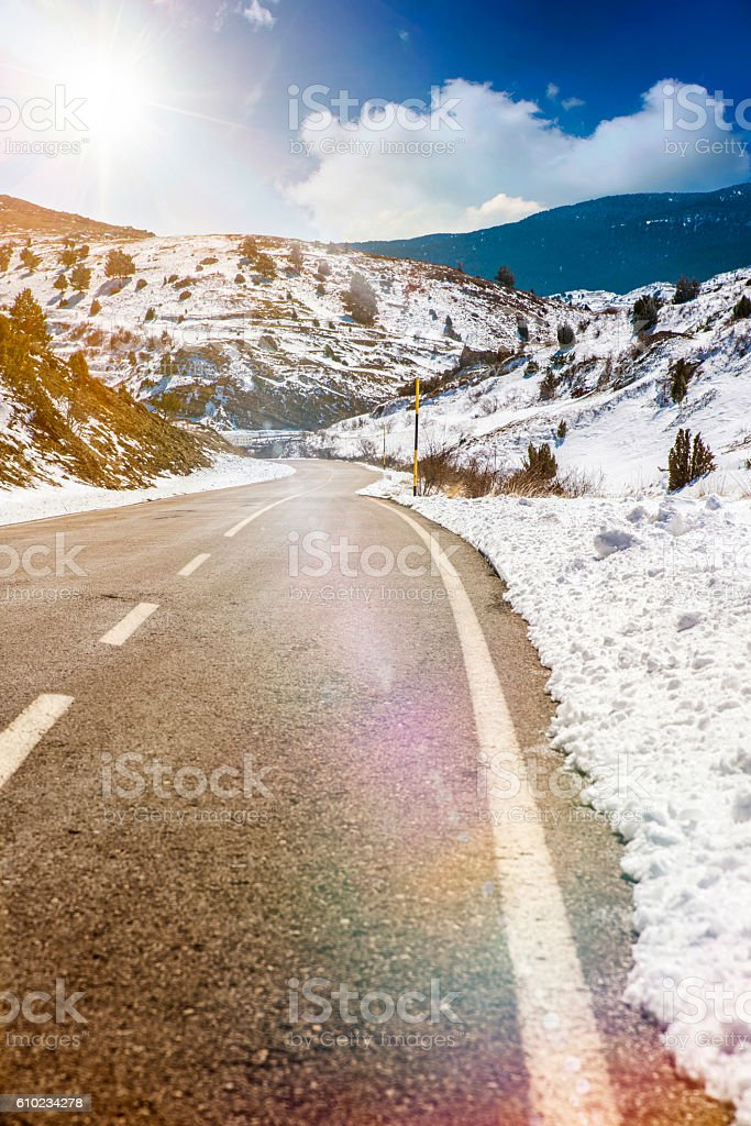 Snowy mountain road and sun stock photo